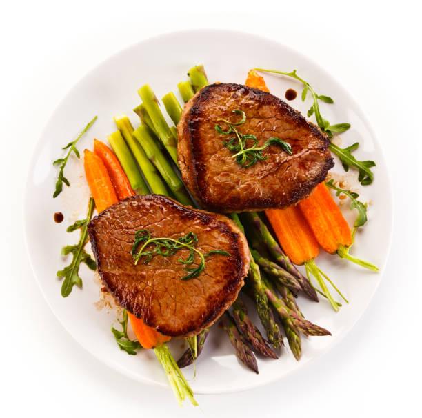 gegrilltes steak mit spargel auf weißem hintergrund - schnitzel braten stock-fotos und bilder