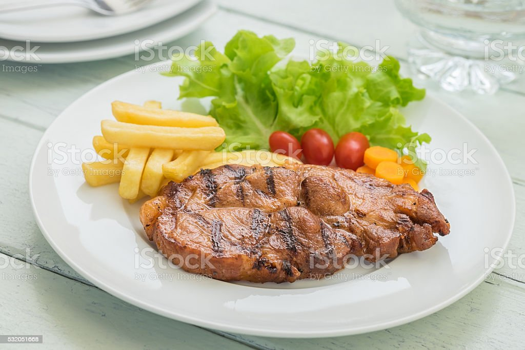 Grilled steak with french fries and vegetables on plate stock photo
