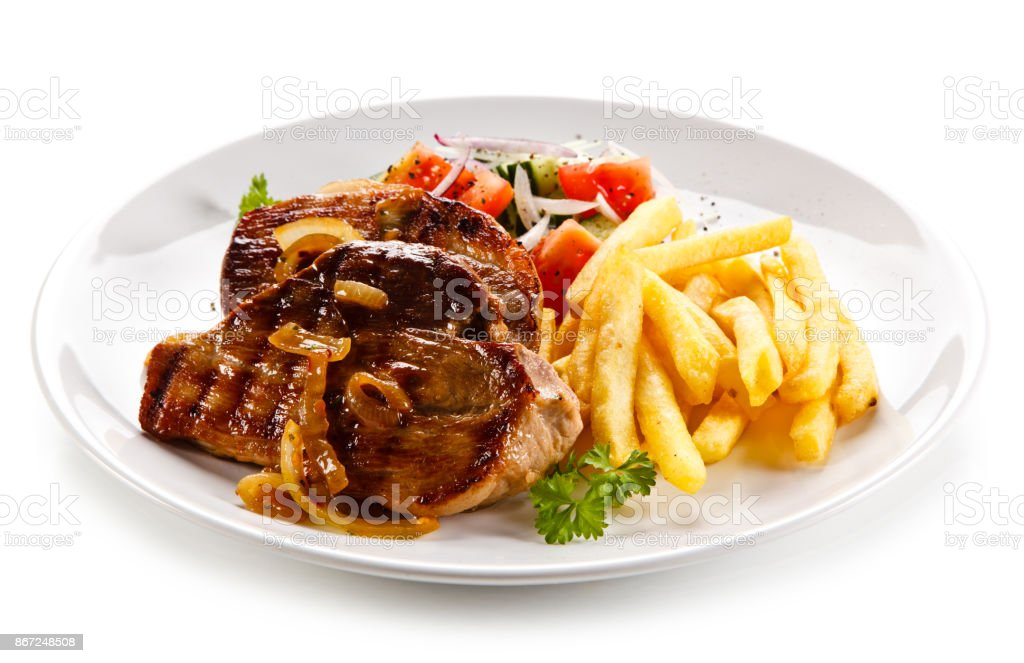 Grilled steak with French fries and vegetables stock photo
