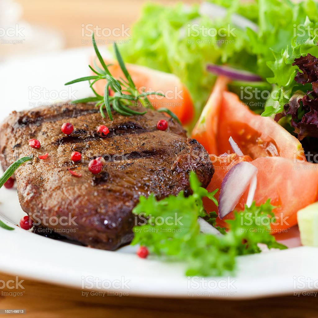Grilled steak with fresh vegetables and herbs royalty-free stock photo