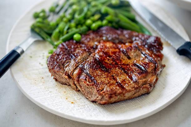 gegrilltes steak mit grünem gemüse - steak anbraten stock-fotos und bilder