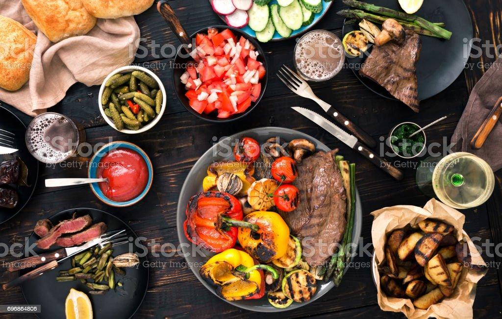 Gegrilltes Steak mit gegrilltem Gemüse, Bier und Wein auf einem dunklen Holztisch, Ansicht von oben – Foto