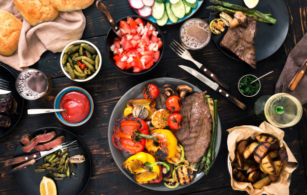 grilled steak with grilled vegetables, beer and wine on a dark wooden table, top view - sport set competition round stock photos and pictures