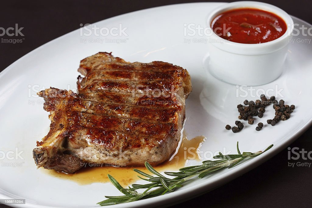 Grilled steak with peppercorns and rosemary sprig royalty-free stock photo