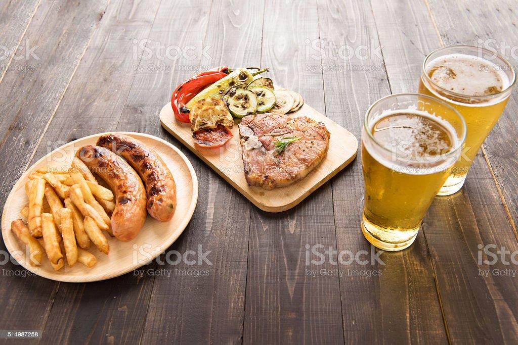 Bistec a la parrilla con una ensalada y cerveza y papas fritas, salchichas - foto de stock