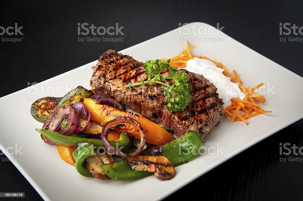 Grilled steak with vegetables on a white plate royalty-free stock photo