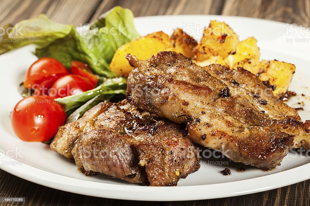 Grilled steaks, baked potatoes and vegetables stock photo