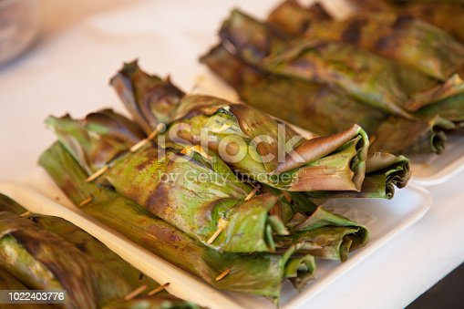 Grilled Steamed Seafood curry fish, shrimps and squid in coconut milk cakes wrapped in banana leaves. Traditional roasted Thai sea food menu.