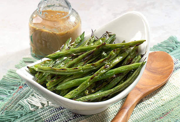 Grilled String Beans Side dish of grilled string beans on table setting. Vinaigrette dressing and wooden spoon vinaigrette dressing stock pictures, royalty-free photos & images