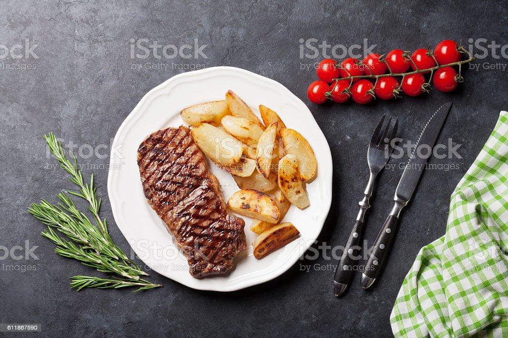 Grilled striploin steak and roasted potato stock photo
