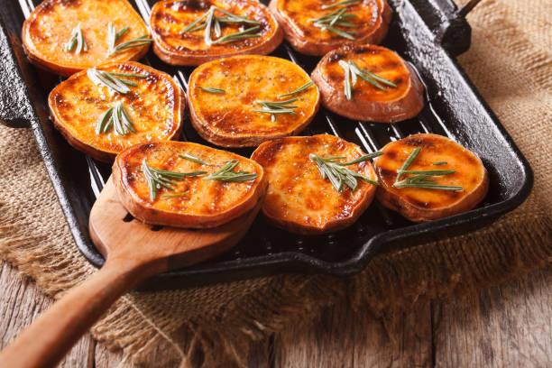 grillowane słodkie ziemniaki z rozmarynem na patelni grillowej z bliska. poziomy - słodki ziemniak zdjęcia i obrazy z banku zdjęć