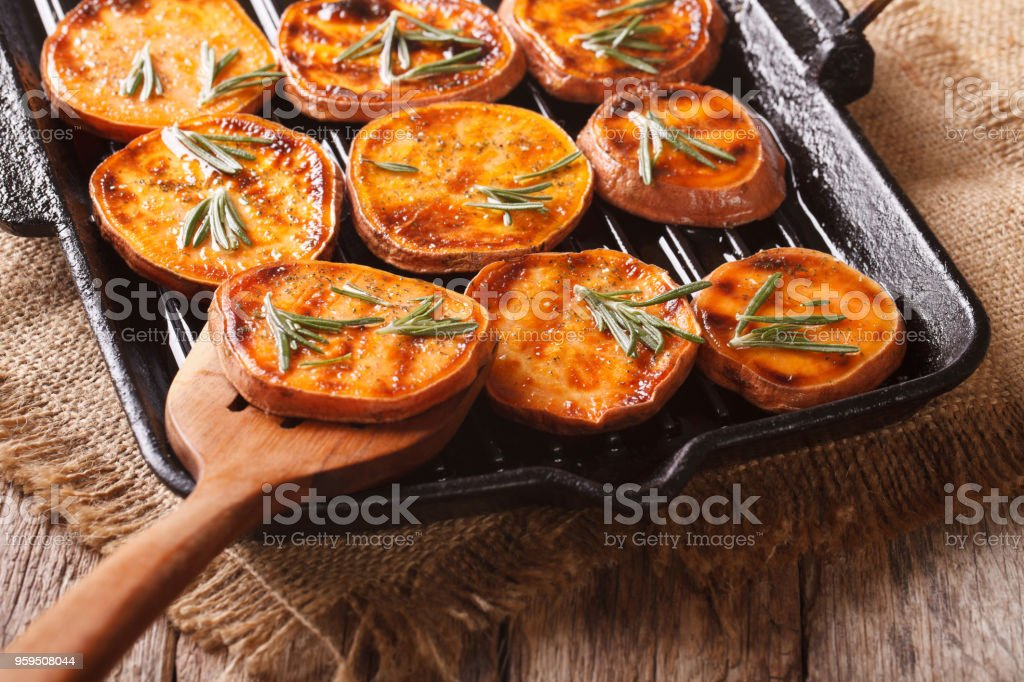 Grilled sweet potatoes with rosemary on the grill pan close-up. horizontal stock photo