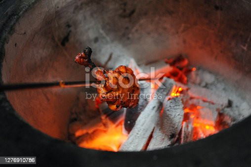 High angle view marinated chicken cooking in an open tandoori Indian oven