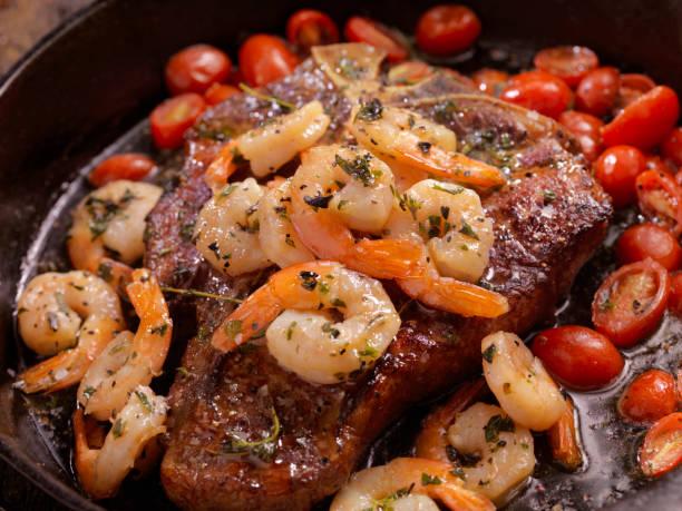 gegrilltes t-bone steak mit garnelen scampi - steak anbraten stock-fotos und bilder
