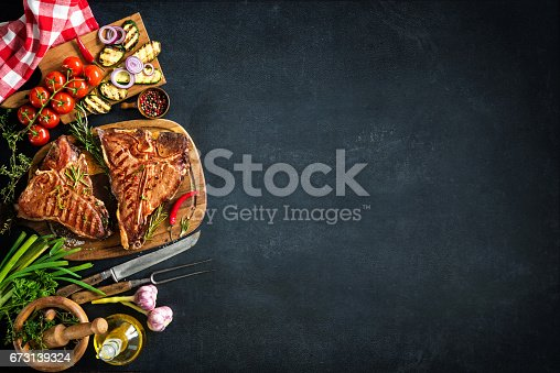 istock Grilled T-bone steaks with fresh herbs and vegetables 673139324
