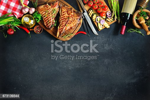 istock Grilled T-bone steaks with fresh herbs and vegetables 673139344