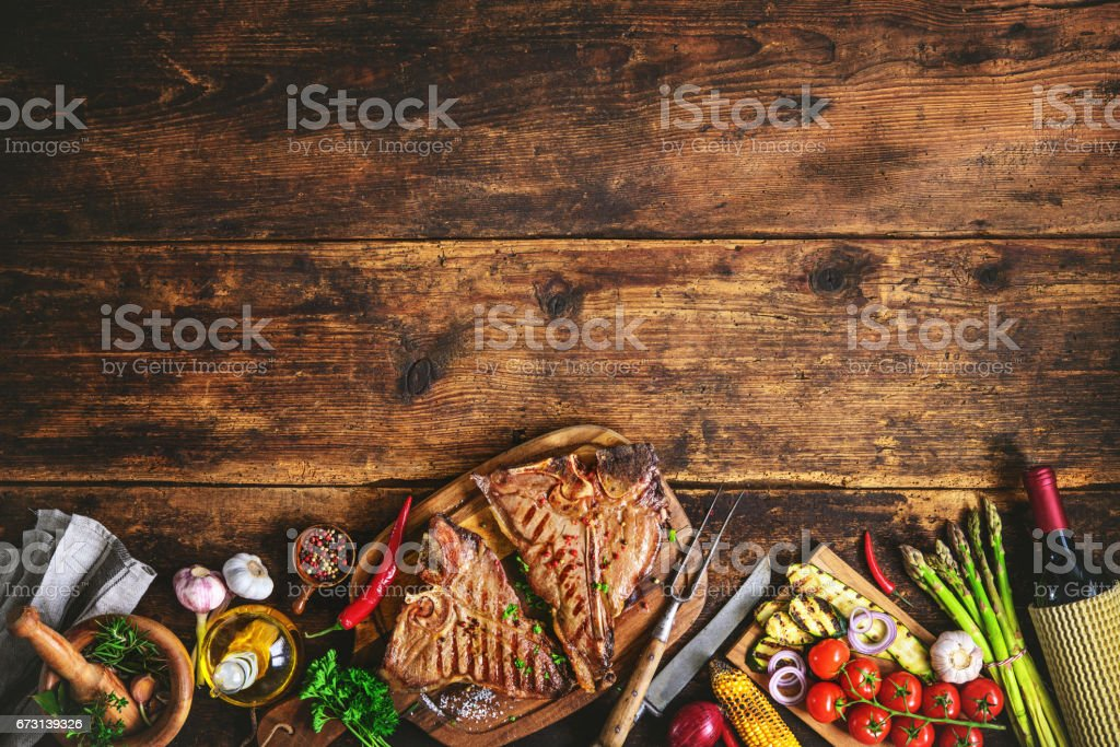 Grilled T-bone steaks with fresh herbs, vegetables ans wine bottle stock photo