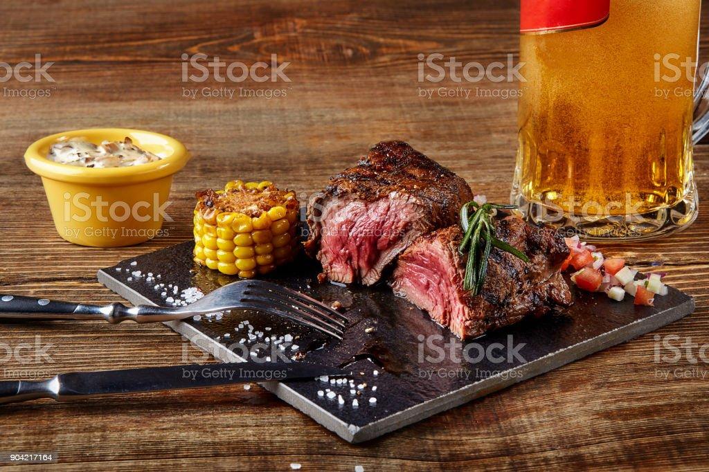 Lombinho grelhado molho de rosbife e cogumelos bife na tábua preto e vidro de cerveja no fundo de madeira - foto de acervo