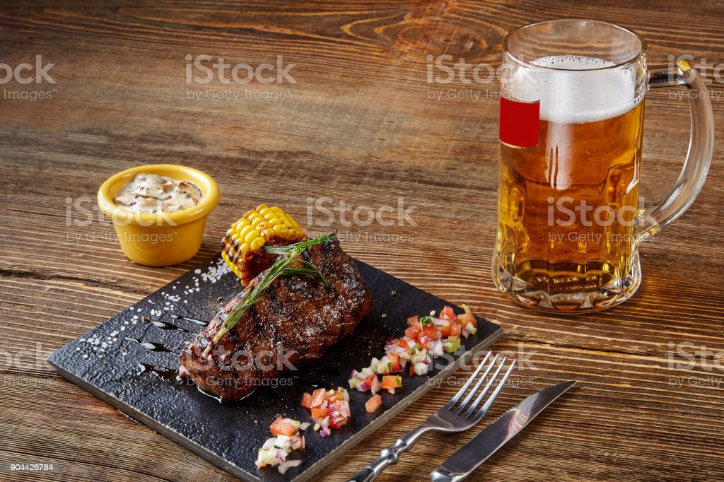 Grilled tenderloin Steak roastbeef and mushrooms sauce on black cutting board and glass of beer on wooden background stock photo