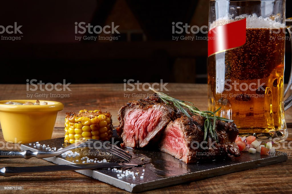 Grilled tenderloin Steak roastbeef and mushrooms sauce on black cutting board and glass of beer on wooden table stock photo