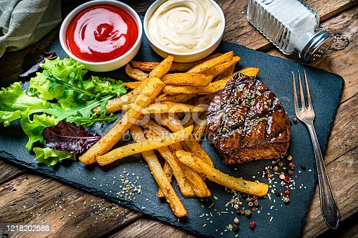 Grilled tenderloin with French fries and salad served on a slate board. Two bowls with ketchup and mayonnaise are at the top of an horizontal frame. A salt shaker complete the composition. High angle view. High resolution 42Mp studio digital capture taken with SONY A7rII and Zeiss Batis 40mm F2.0 CF lens