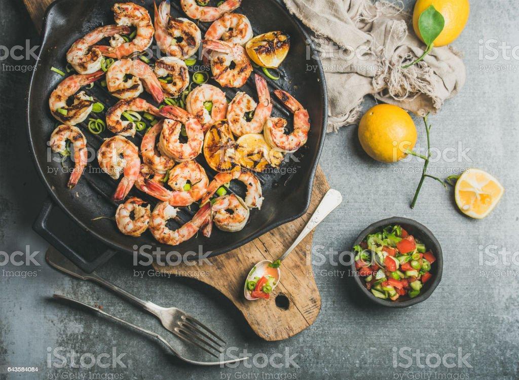 Grilled tiger prawns in pan with lemon, leek, chili, sauce stock photo
