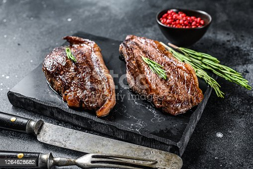 Grilled top sirloin cap or picanha steak on a stone chopping Board. Black background. Top view.