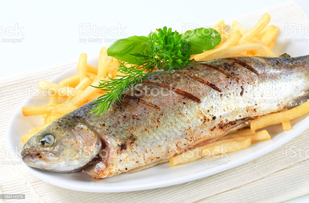 Grilled trout with French fries royalty-free stock photo