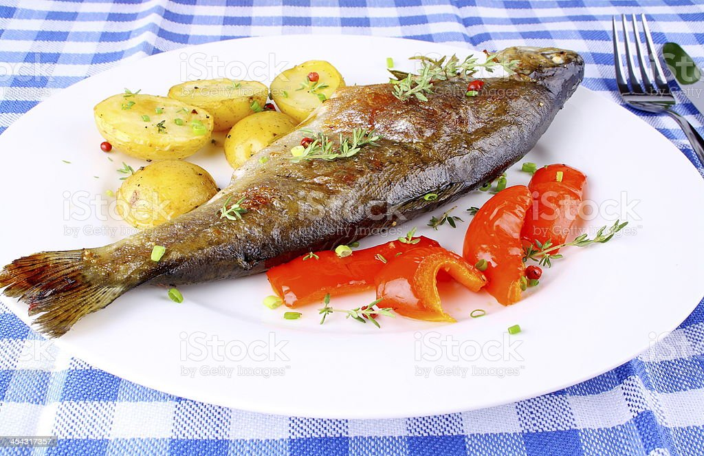 Grilled trout with potato and red peppers royalty-free stock photo