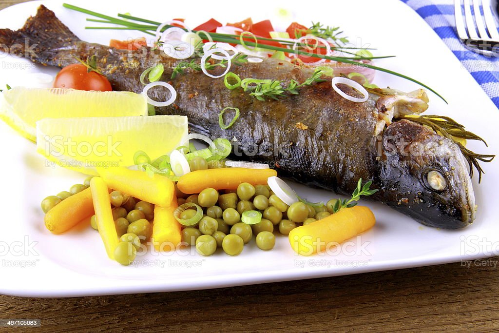 Grilled trout with quite fine vegetables and cutlery royalty-free stock photo