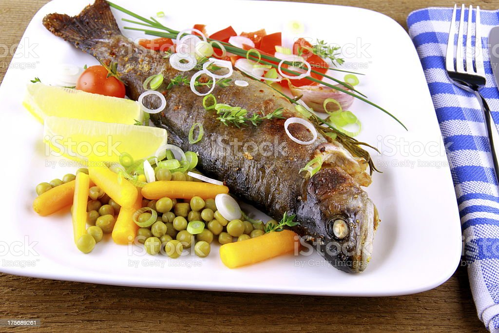Grilled trout with quite fine vegetables, cutlery royalty-free stock photo