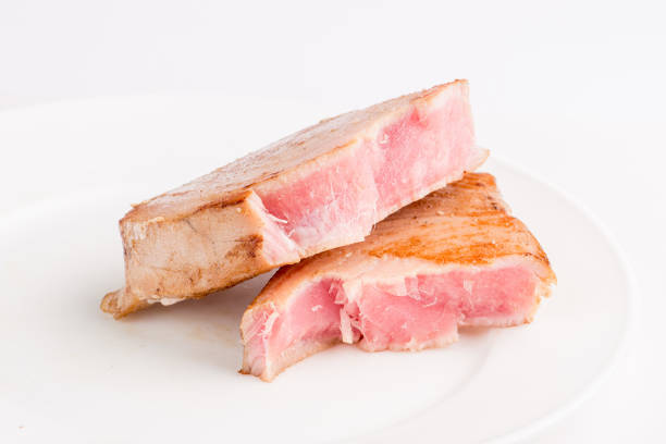 grilled tuna fish steak on a white plate with a place for garnish stock photo