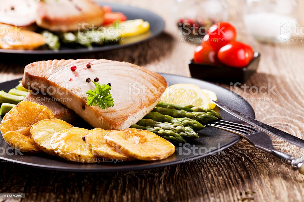 Grilled tuna steak served on asparagus with roasted potatoes stock photo