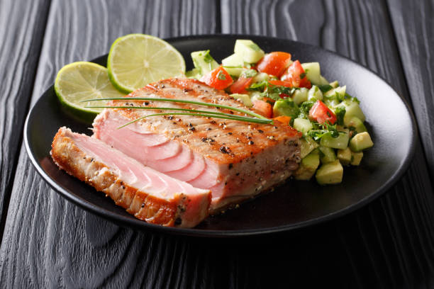 Grilled tuna steak with pepper and avocado cucumber salsa close-up. horizontal stock photo