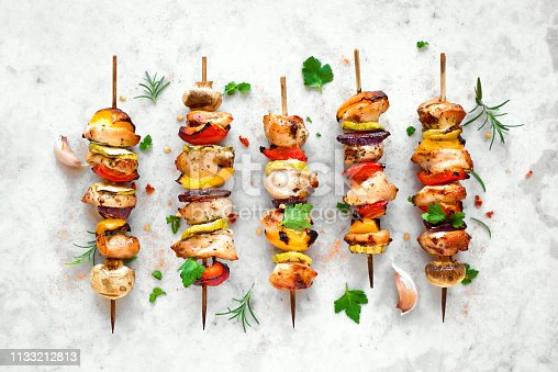 Grilled vegetable and chicken skewers with  bell peppers, zucchini, onion and mushrooms on white marble background, top view. Meat and vegetables kebabs on skewers.