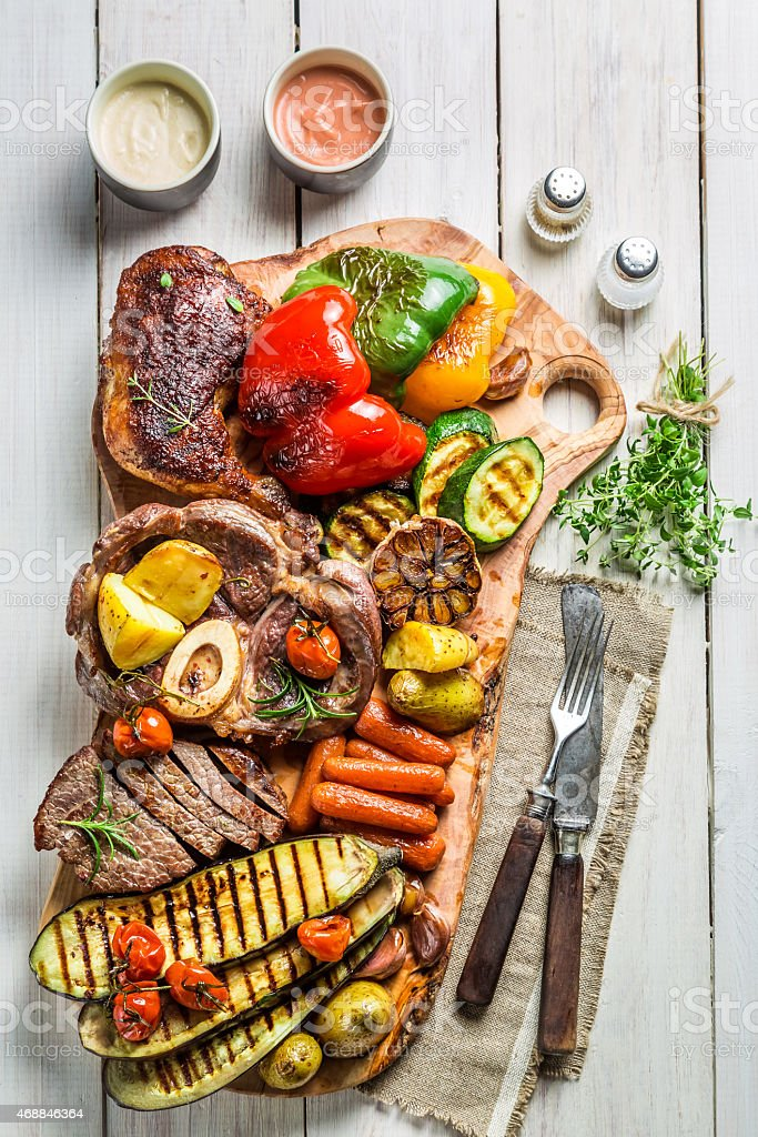 Grilled vegetables and steak with salt on wooden board stock photo