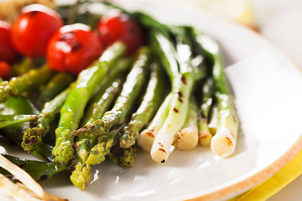 grilled vegetables - asparagus, onions, peas, tomatoes stock photo