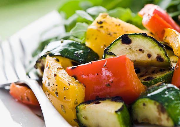 Grilled vegetables Plate of grilled vegetables with arugula salad on a green background yellow bell pepper stock pictures, royalty-free photos & images