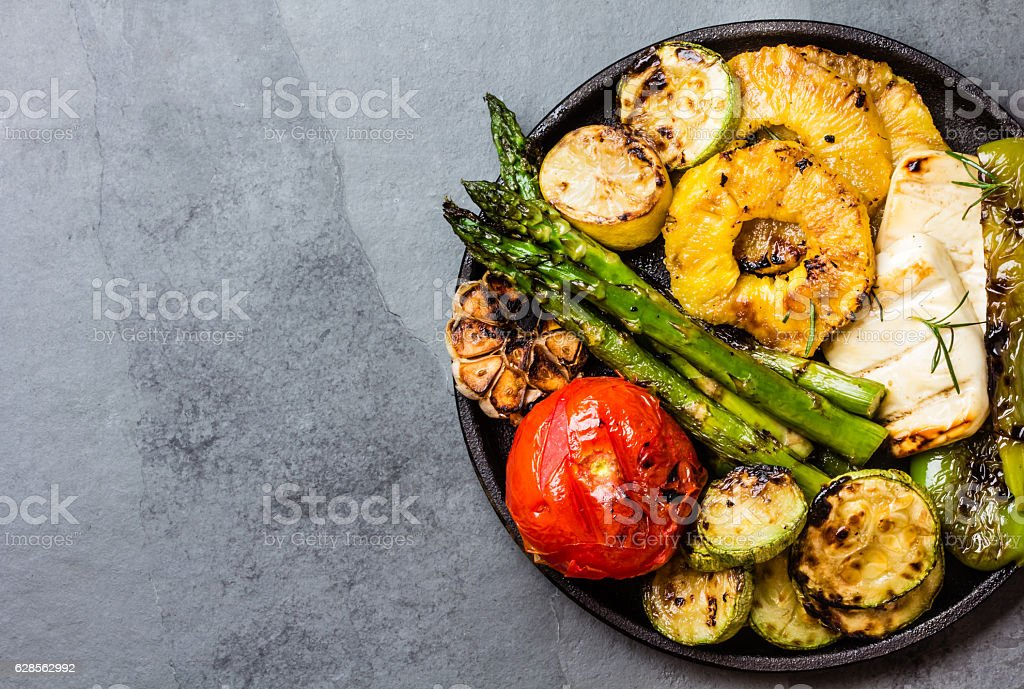 Grilled vegetables, pineapple slices and fresh cheese on iron plate stock photo