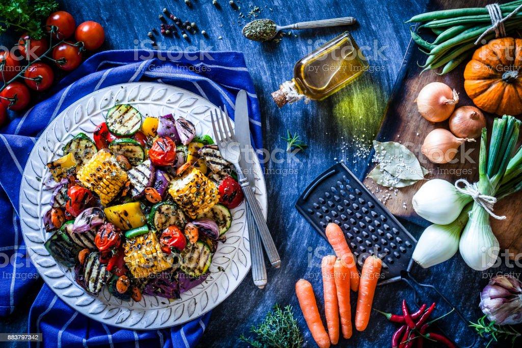 Prato de legumes grelhados, atirou por cima, na mesa da cozinha azulada - foto de acervo