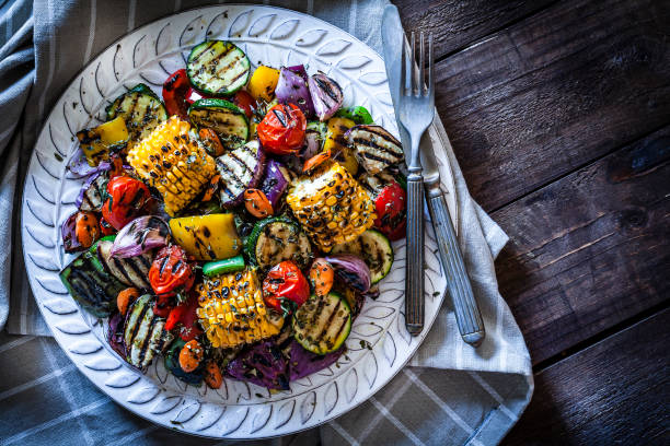 grilled vegetables plate shot from above on rustic wooden table - grilled vegetables stock photos and pictures