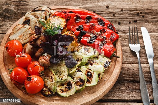 655793486 istock photo Grilled vegetables served on wood platter top view 655794440