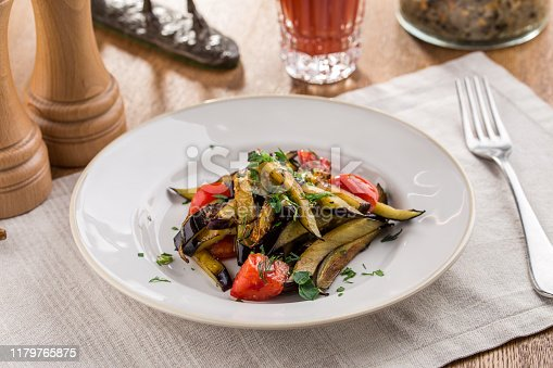 655793486 istock photo Grilled vegetables warm salad with eggplant and tomato with tomato juice on wooden table 1179765875