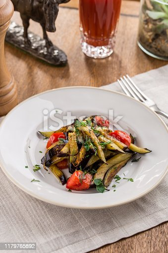 655793486 istock photo Grilled vegetables warm salad with eggplant and tomato with tomato juice on wooden table 1179765892