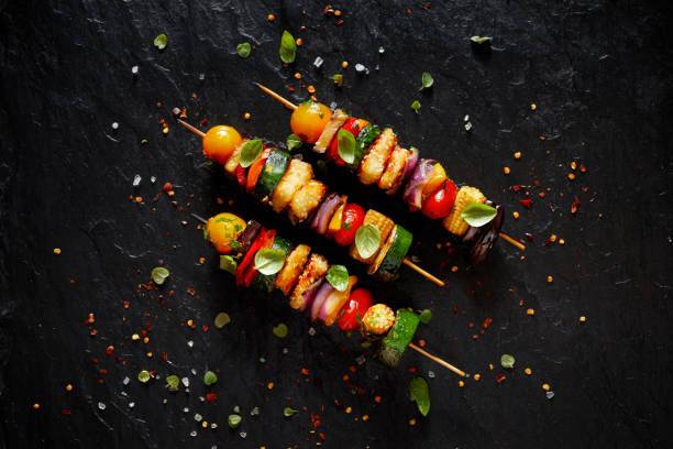gegrillte vegetarische spieße mit halloumi-käse und gemischtem gemüse auf schwarzem hintergrund - spieße grillen stock-fotos und bilder
