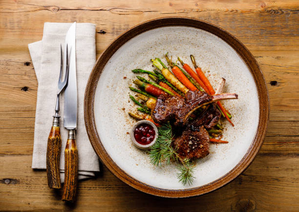 Grilled Venison Ribs with baked vegetables and berry sauce on wooden background stock photo