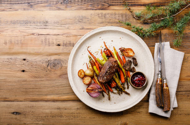 Grilled Venison Steak with baked vegetables and berry sauce on wooden background copy space