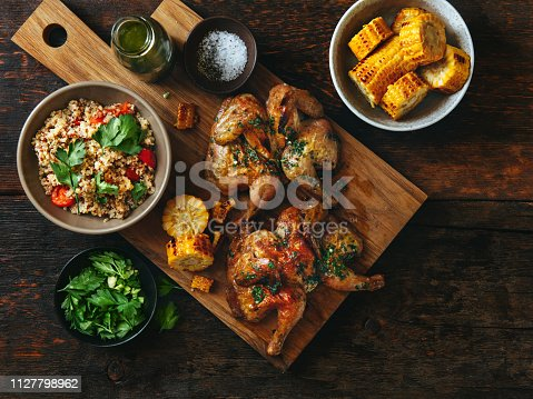 Grilled whole butterflied chickens with vegetables, chimichurri sauce and quinoa salad