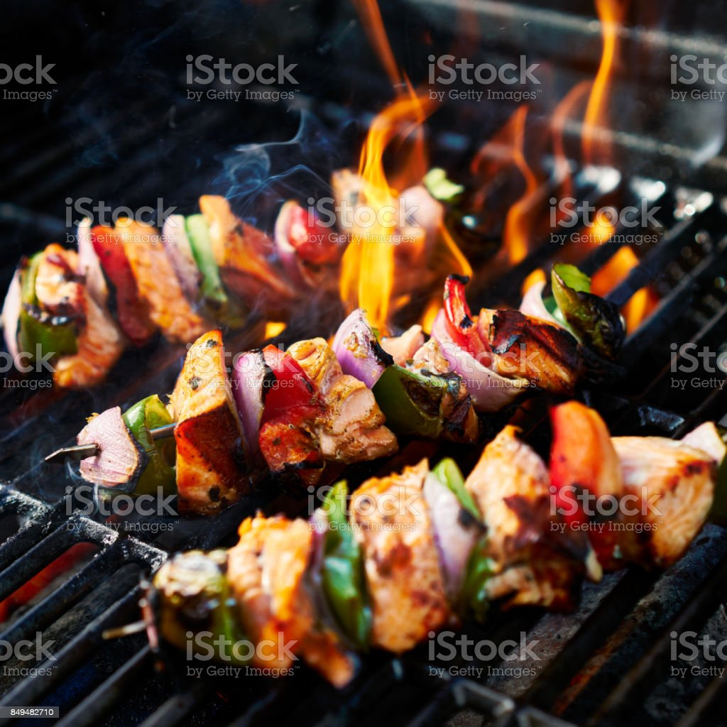 grilling chicken kabobs on flaming grill stock photo