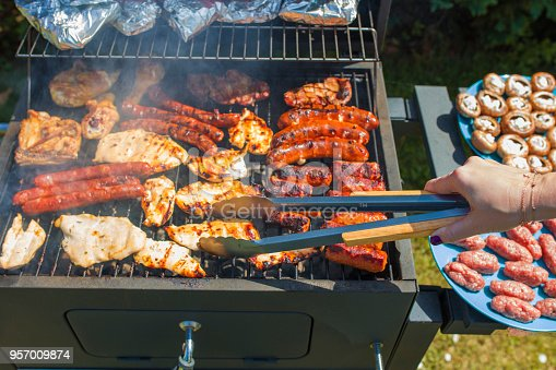 istock Grilling food on barbecue grill, hands preparing skewers 957009874